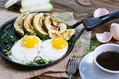 Selbst gemachtes Frühstück - durcheinandergemischte Eier, Zucchinischeiben und schwarzer Kaffee Stockfotografie