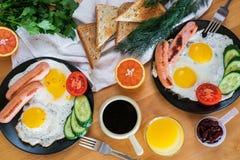 Selbst gemachtes Frühstück mit Spiegeleitoastwurst-Fruchtgemüsekaffee und Orangensaft in der Draufsichtebene legen Konzept Lizenzfreies Stockfoto