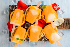 Selbst gemachtes gefrorenes Eiscremeeis am stiel gemacht mit oragnic frischen Orangen auf hölzernem Hintergrund, Lizenzfreie Stockbilder