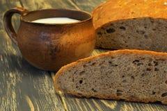 Selbst gemachtes geschmackvolles weiches wohlriechendes rötliches Roggenbrot und Lehmschale mit Milch auf dunklem natürlichem höl stockbild