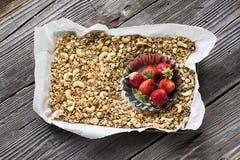 Selbst gemachtes Granola mit Acajoubaum und frischen Erdbeeren zum ein gesundes selbst gemachtes Frühstück in einem Backblech auf Lizenzfreie Stockbilder