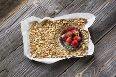 Selbst gemachtes Granola mit Acajoubaum und frischen Erdbeeren zum ein gesundes selbst gemachtes Frühstück in einem Backblech auf Stockfoto
