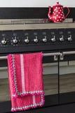 Selbst gemachtes Häkelarbeit-Geschirrtuch, das an einem Ofen hängt Stockfoto