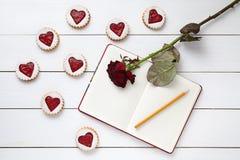 Selbst gemachtes Herz des Kekses formte Plätzchen mit leerem Notizbuch, Bleistift und rosafarbener Blume auf weißem hölzernem Hin Stockfotografie