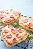 Selbst gemachtes Herz formte die Pepperoniminipizzas, die mit Basilikum gedient wurden lizenzfreies stockbild