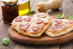 Selbst gemachtes Herz formte Minipizzas mit Pepperonis lizenzfreies stockfoto
