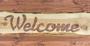 Selbst gemachtes Holzschild mit dem englischen Wort für Willkommen lizenzfreie stockfotografie