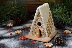 Selbst gemachtes Lebkuchenhaus mit Kiefernniederlassungen, -kegeln und -keksen auf dunklem Hintergrund Europäische Weihnachtstrad Stockbild