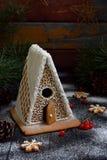 Selbst gemachtes Lebkuchenhaus mit Kiefernniederlassungen, -kegeln und -keksen auf dunklem Hintergrund Europäische Weihnachtstrad Lizenzfreie Stockbilder