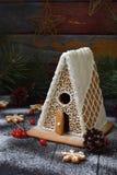 Selbst gemachtes Lebkuchenhaus mit Kiefernniederlassungen, -kegeln und -keksen auf dunklem Hintergrund Europäische Weihnachtstrad Lizenzfreie Stockfotografie