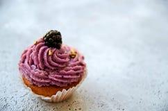 Selbst gemachtes Muffin in einem Braun backte Korb mit purpurroter Creme, frische Brombeere, goldenes Spritzen auf unscharfem Hin stockfotos