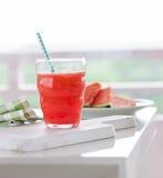 Selbst gemachtes saftiges kaltes Getränk mit Wassermelone und Wasser in einem Glas mit blauem Stroh auf einem hölzernen Schnitt v Stockbild