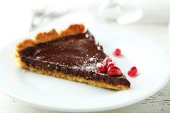 Selbst gemachtes Schokoladentörtchen mit Granatapfel auf einem weißen hölzernen Hintergrund Lizenzfreie Stockbilder
