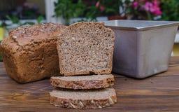 Selbst gemachtes Schwarzbrot mit etwas Brot schneidet das Lügen auf Holzoberfläche Lizenzfreie Stockfotografie