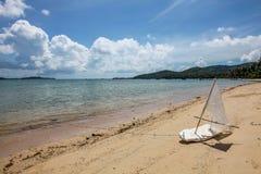Selbst gemachtes Spielzeugboot auf sandigem Strand nahe dem Meer Lizenzfreies Stockfoto