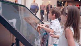 Selbstbedienung, Kinderfreunde benutzt elektronischen Führer zu Suchinformation über Standort des Shops am Einkaufszentrum stock footage
