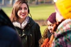 Selbstbewusste junge Frau draußen umgeben von den Freunden Stockfotografie