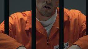 Selbstbewusster krimineller kauender Zahnstocher hinter Gefängnisstangen, Kopf der Mafia stock video