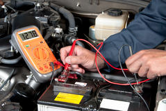 Selbstmechaniker, der Autobatteriespannung überprüft Stockfotos