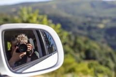 Selbstporträt in einem Rückspiegel eines Autos mit Landschaftshintergrund Stockbild
