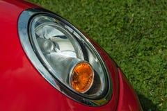 Selbstscheinwerfer auf einem roten Auto mit Hintergrund des grünen Grases Stockbilder