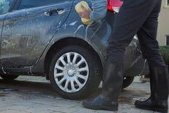 Selbstservice-Personal, das ein Auto mit Schwamm wäscht Lizenzfreie Stockbilder