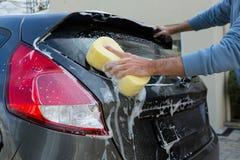 Selbstservice-Personal, das ein Auto mit Schwamm wäscht Stockfotografie