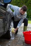 Selbstservice-Personal, das einen Autoreifen mit Schwamm wäscht Lizenzfreies Stockbild