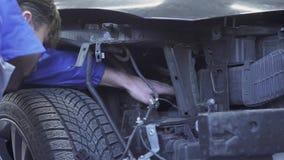 Selbstspezialist, der eine Prüfung vom Auto nach einem Unfall, Kontrollsuspendierungsaufnahme-Reparaturangaben im Auto macht stock footage