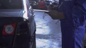 Selbstspezialist, der eine Prüfung vom Auto nach einem Unfall, notierende Reparaturangaben im Autoservice macht stock video