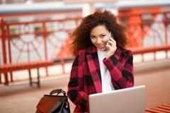 Selbstständige Frau, die mit ihrem Telefon und Laptop in einer Restaurantterrasse arbeitet lizenzfreies stockbild
