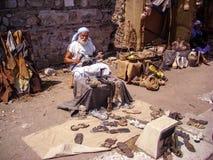 Selcuk, Турция - 18-ое июня 2012: Актер представляя как старый создатель ботинка ремесленника в древнем городе Ephesus, около Kus стоковые фото
