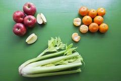 Selderie, appel en mandarijn op de houten achtergrond stock foto's