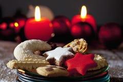 Seleção de cookies do Natal na placa em velas ardentes do assoalho de madeira no fundo Fotografia de Stock