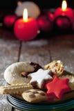 Seleção de cookies do Natal na placa em velas ardentes do assoalho de madeira no fundo Imagens de Stock