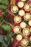 A seleção do Natal de mini tritura tortas e folhas do azevinho Foto de Stock