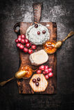 Seleção do queijo macio com molho da uva e de mostarda do mel na placa de corte rústica no fundo escuro Foto de Stock
