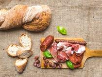 Seleção dos aperitivos da carne e um naco do pão rústico da vila sobre Fotos de Stock