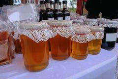 Seleção dos frascos do mel com as partes superiores laçado indicadas em um villag Fotos de Stock