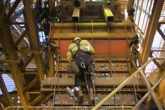 Sele för säkerhet för manlig arbetare för reptillträdesbransch bärande, hängande arbeta för nedgångskyddshjälm på position för y- royaltyfri foto