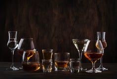 Selección de bebidas alcohólicas fuertes duras en vidrios grandes y pequeño vaso de medida en assortent: vodka, coñac, tequila, b imagen de archivo libre de regalías