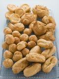 Selección de bollos de los pasteles de los Choux en un estante de enfriamiento Fotos de archivo