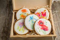Selección de galletas hermosas con las flores pintadas en la caja de madera Fotos de archivo