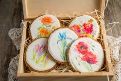 Selección de galletas hermosas con las flores pintadas en la caja de madera Fotografía de archivo