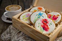 Selección de galletas hermosas con las flores pintadas en la caja de madera Imagen de archivo