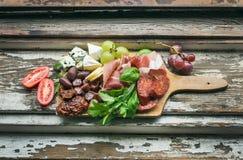 Selección de los aperitivos de la carne en el viejo fondo de madera pintado Imagen de archivo