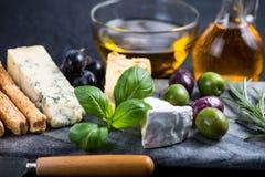 Selección del queso del estilo de los Tapas con las aceitunas, las uvas y las hierbas Fotos de archivo libres de regalías