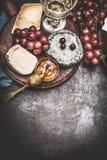 Selección del queso en la placa rústica con el vino, la uva y la salsa de mostaza de la miel, fondo oscuro del vintage, visión su Fotografía de archivo libre de regalías