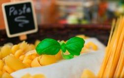 Selección secada mezclada de las pastas con la albahaca, comida italiana Imagen de archivo