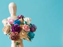 Seleccione el foco de la flor La marioneta de madera lleva a cabo la flor y la situación en la tabla de madera el fondo es azul y Fotografía de archivo